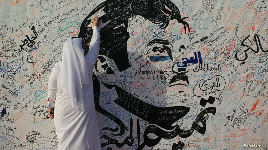 A man writes on a painting depicting Qatar's Emir Sheikh Tamim bin Hamad Al Thani in Doha, Qatar, July 2, 2017. The artwork has attracted comments of support from residents amid a diplomatic crisis between Qatar and neighboring Arab countries.