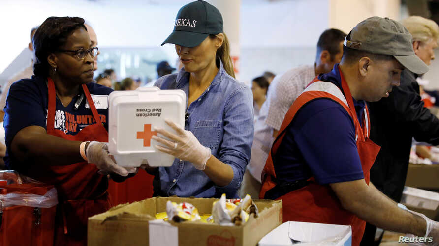 First lady Melania Trump helps a volunteer hand out meals during a visit with flood survivors of Hurricane Harvey at a relief center in Houston, Texas, Sept. 2, 2017.