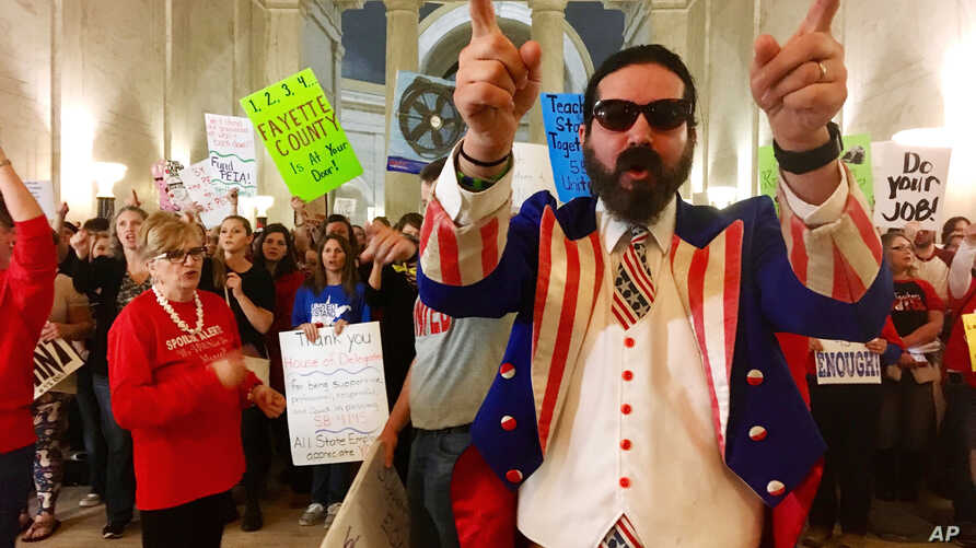 Parry Casto, a fifth-grade teacher at the Explorer Academy in Huntington, W.Va., dressed in an Uncle Sam costume, leads hundreds of teachers in chants outside the state Senate chambers at the Capitol in Charleston, W.Va., March 1, 2018.  Senators ref