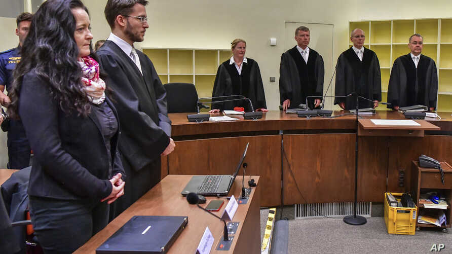 Suspect Beate Zschaepe (L) stands beside her lawyer Mathias Grasel (2nd-L) before Presiding Judge Manfred Goetzl, second from right, speaks the verdict in the court in Munich, southern Germany, July 11, 2018.