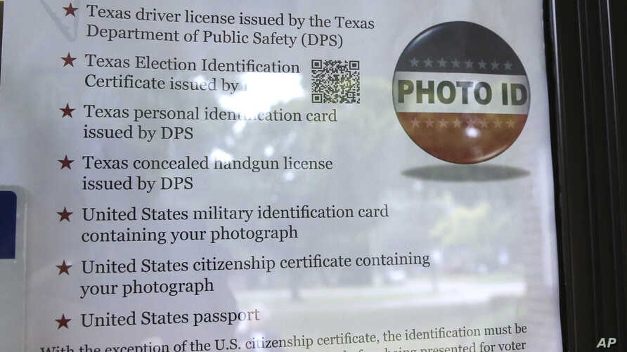 FILE - A sign in a window tells of photo ID requirements for voting at a polling location in Richardson, Texas, Nov. 5, 2013. The Trump administration says Texas has rid its voter ID law of any discriminatory effects and is asking a judge who once co