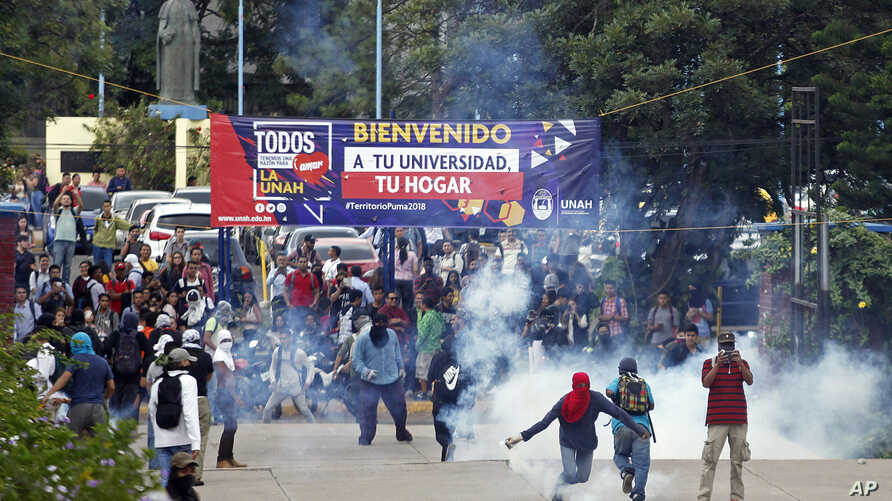 FILE - Some engulfed in teargas, students and other protestors confront riot police outside the university during a protest against President Juan Orlando Hernandez in Tegucigalpa, Feb. 5, 2018.