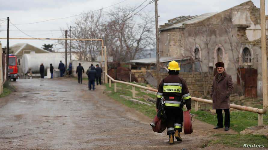 A firefighter carrying fire hoses walks near the scene of a fire that broke out in a drug abuse treatment center in Baku, Azerbaijan, March 2, 2018.