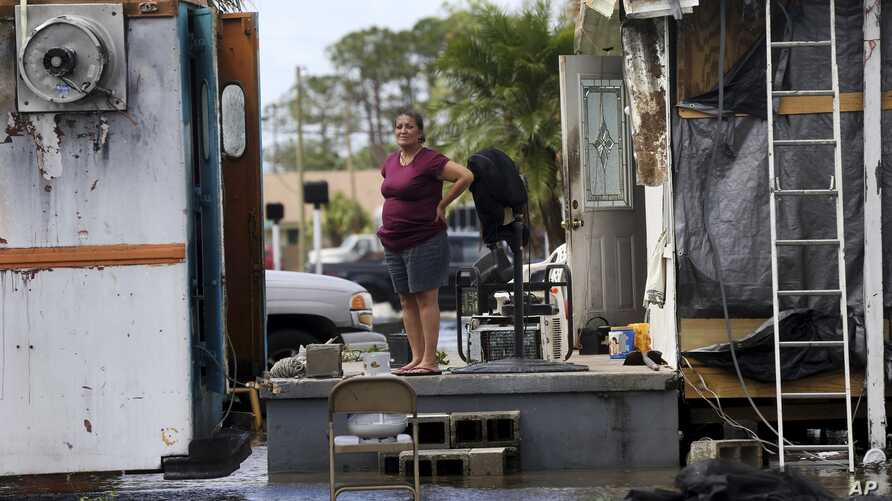 Elida Dimas looks at floodwaters from her porch, in the aftermath of Hurricane Irma, in Immokalee, Florida, Sept. 11, 2017.