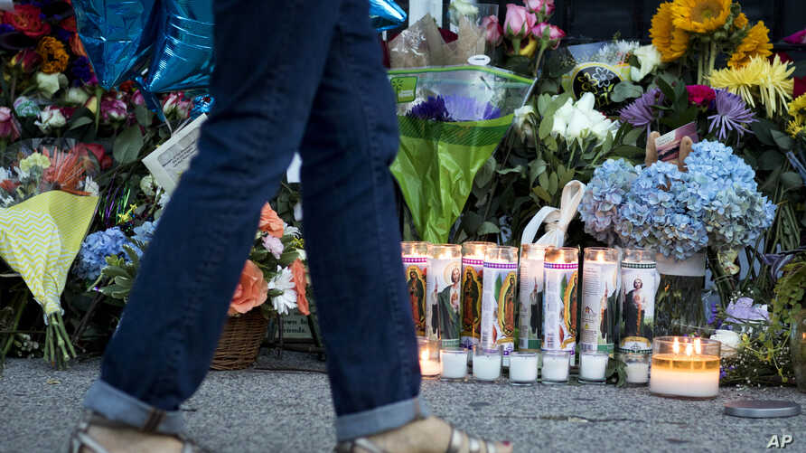 FILE - A woman walks past prayer candles left in front of the Emanuel AME Church in Charleston, South Carolina, several days after nine people were shot and killed during a Bible study, June 20, 2015.