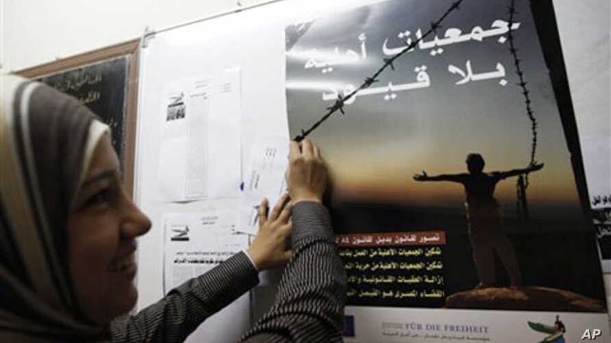 "A female staff member of the Egyptian Organization For Human Rights hangs a poster that reads in Arabic ""Unrestricted Non-Governmental Organizations"" at their office in preparation for the November 28 parliamentary elections, in Cairo, 21 Nov 2010"