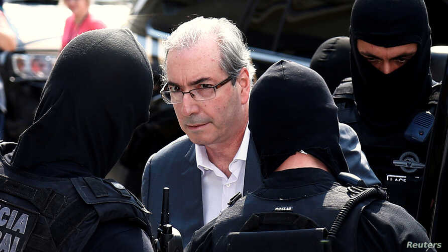 Former speaker of Brazil's Lower House of Congress, Eduardo Cunha (C), is escorted by federal police officers as he leaves the Institute of Forensic Science in Curitiba, Brazil, Oct. 20, 2016.