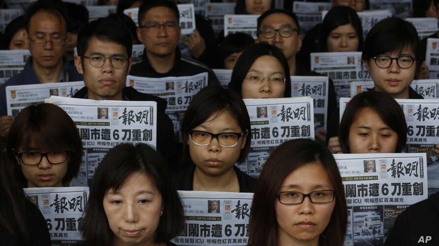 Staff members of the Mingpao newspaper hold their newspaper, with the headline on the former editor Kevin Lau, who was assaulted and injured, during a protest outside the Mingpao office in Hong Kong, Feb. 27, 2014.