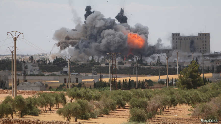 Smoke and flame rise after what fighters of the Syria Democratic Forces (SDF) said were U.S.-led air strikes on the mills of Manbij where Islamic State militants are positioned,  in Aleppo Governorate, Syria, June 16, 2016.