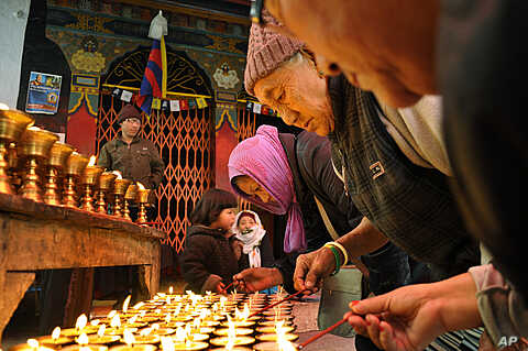 Tibetan Buddhist exiles offer prayers as they light butter lamps to show solidarity with Tibetans who have either set themselves on fire or were allegedly injured or killed in clashes with Chinese police, in New Delhi, India, February 9, 2012.