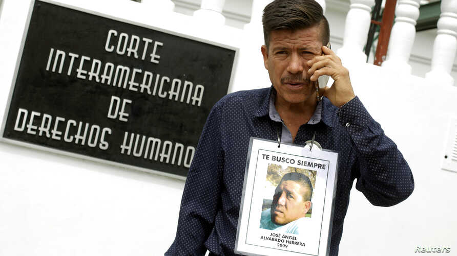 Jaime Alvarado displays a portrait of his brother Jose Angel Alvarado, who went missing in 2009, allegedly as a result of human rights violations by the Mexico military, during a hearing convened by the judges of the Inter-American Court of Human Rig