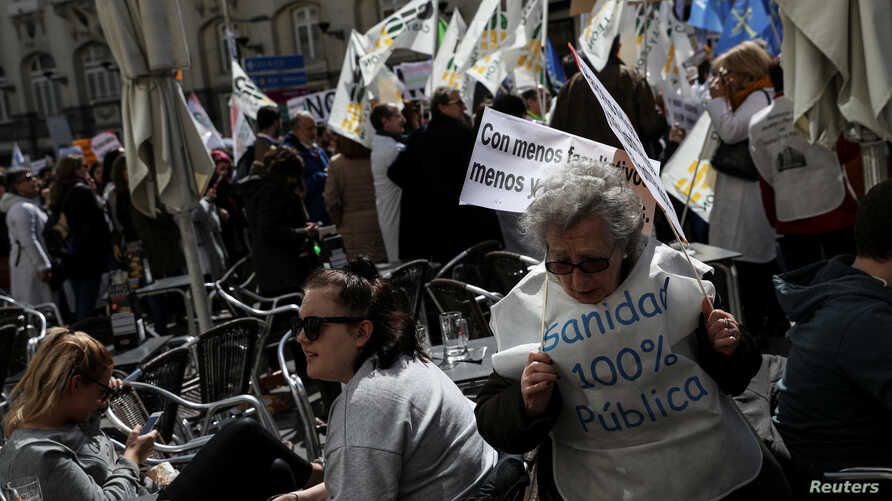 """A woman wearing a vest reading """"100% public health care"""" attends a protest by doctors to demand better salaries and working conditions, in Madrid, March 21, 2018."""