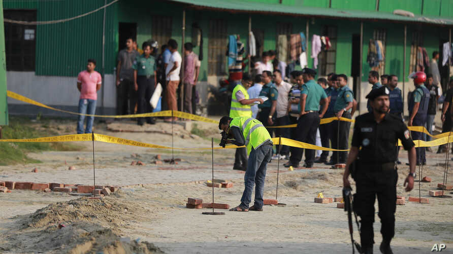 Members of Crime Scene Unit investigate the spot where an unidentified intruder died in a blast after attempting to enter the camp of Rapid Action Battalion (RAB) in Dhaka, Bangladesh, March 17, 2017. Another suspected militant armed with explosives