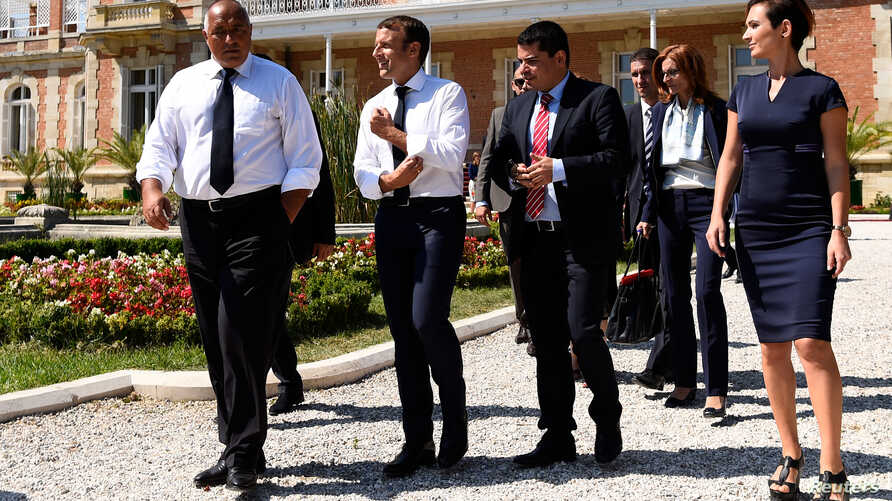 French President Emmanuel Macron (R) rolls up his sleeves as he walks along side Bulgarian Prime Minister Boyko Borissov following a press conference at the Euxinograd Palace on the Black Sea coast just north of the town of Varna, Bulgaria, Aug. 25,