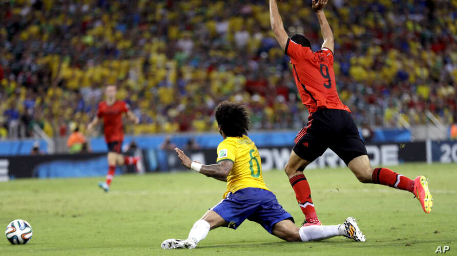 Mexico's Raul Jimenez, right, raises his arms after a challenge on Brazil's Marcelo during the group A World Cup soccer match between Brazil and Mexico at the Arena Castelao in Fortaleza, Brazil, Tuesday, June 17, 2014