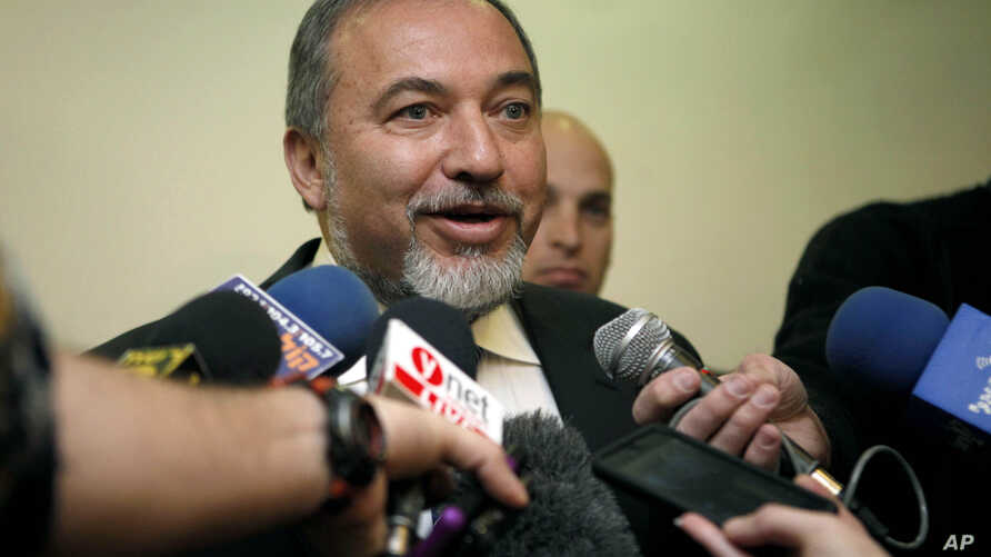 Former Israeli Foreign Minister Avigdor Lieberman speaks to journalists as he arrives to the weekly cabinet meeting at the prime minister's office in Jerusalem, December 16, 2012.