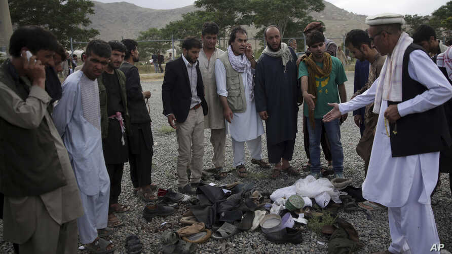 Men try to recognize the victims from the remains of their clothes at the site of three suicide attacks, in Kabul, Afghanistan, Jun 3, 2017.