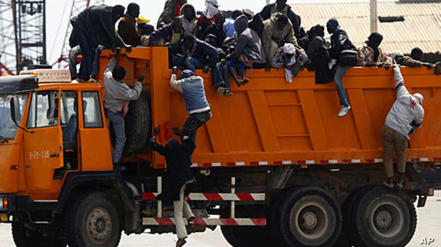 Migrant workers from Africa jump off a truck after arriving in Misrata port during an evacuation operation organized by IOM (International Organization for Migration), April 23, 2011