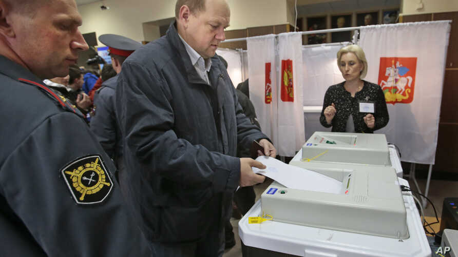 A man casts his ballot paper at a polling station in the town of Khimki outside Moscow, Russia, Oct. 14, 2012.