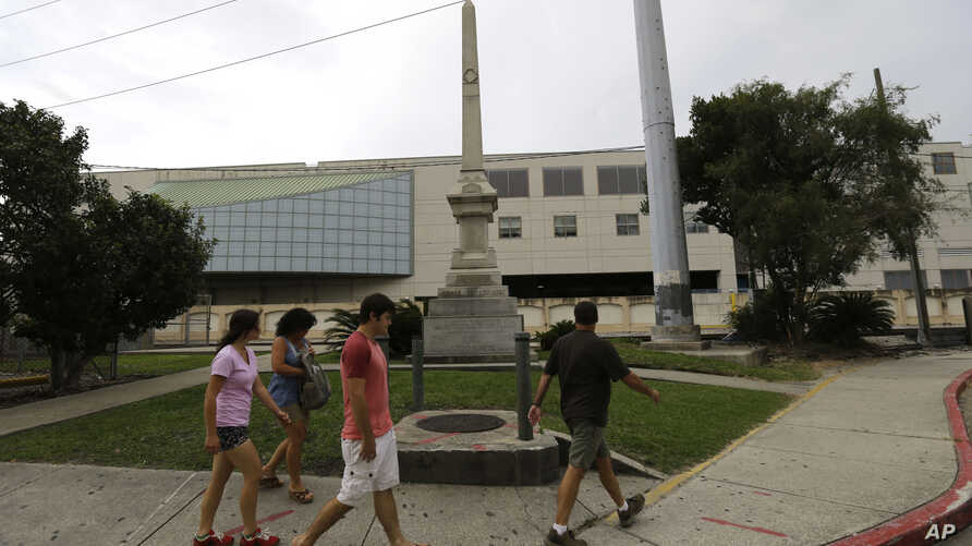 FILE - People walk past the Liberty Place monument in downtown New Orleans, Sept. 2, 2015. In December, the New Orleans City Council voted to remove the obelisk commemorating the Battle of Liberty Place, as well as other Confederate-related statutes