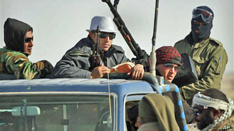 Libyan rebels who are part of the forces against Libyan leader Moammar Gadhafi ride on an armed truck near Ras Lanuf, eastern Libya, March 7, 2011