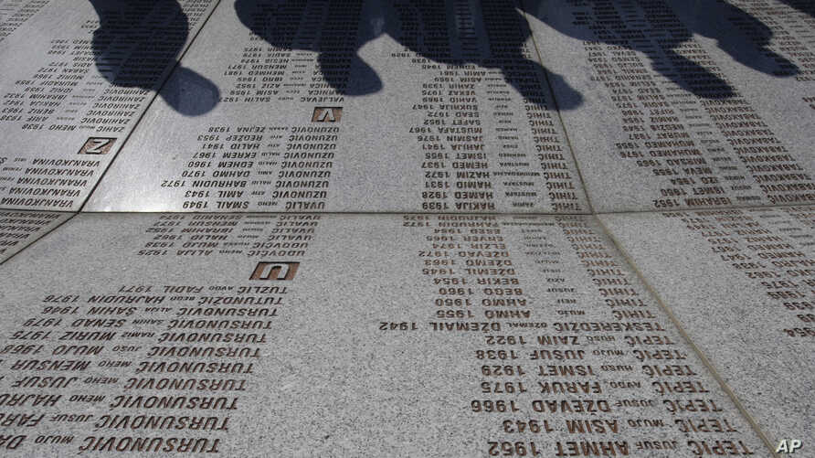 FILE - War veterans from the Balkan war of the 1990's  pay their respects in front of a marble stone with the names of victims at  the memorial center Potocari, near Srebrenica, 150 kms northeast of Sarajevo, Bosnia, Nov.17, 2012.