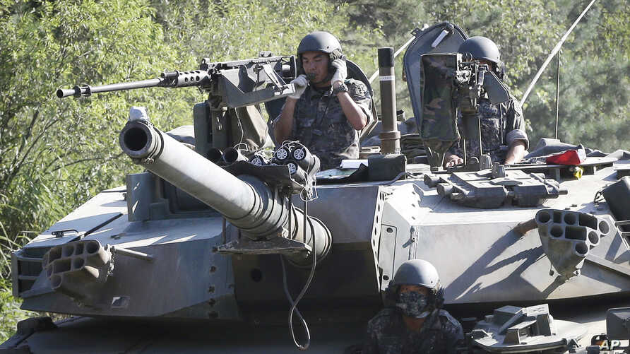 South Korean army soldiers ride a K-1 tank during the annual exercise in Paju, South Korea, near the border with North Korea, Aug. 22, 2016.