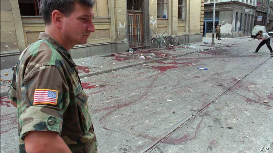 FILE - Lt. Col. Charles Vuckovic Defense Attache of the U.S. embassy in Sarajevo visits the location of the mortar impact near a market place in downtown Sarajevo, Aug. 28, 1995.