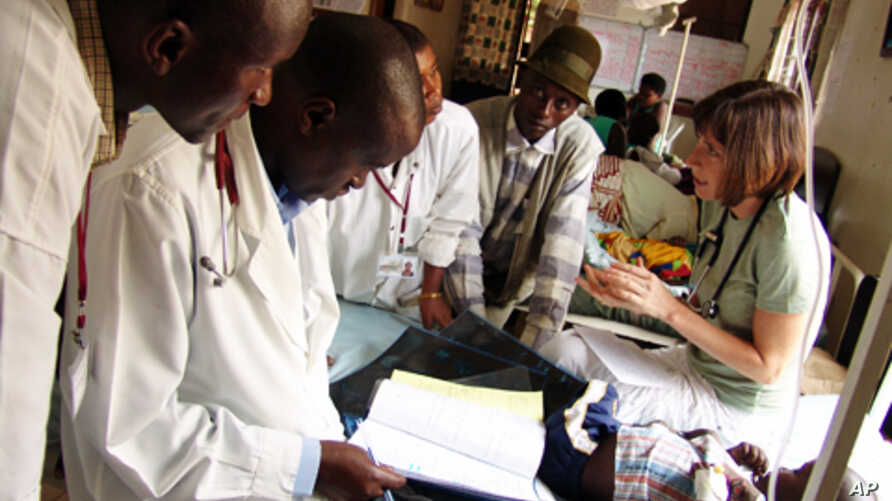 Sara Stulac (right), consults with colleagues at the Rwinkwavu Hospital in Eastern Rwanda. Stulac, director of pediatrics for Partners In Health, has designed a program which brings Rwandan physicians together with Boston-based pediatric oncologists.