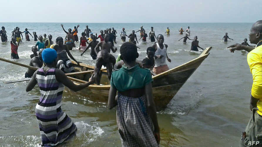 Survivors of a boat accident come back ashore on Lake Albert, on Dec. 26, 2016 in Buliisa, after at least 30 Ugandan members of a village football team and their fans drowned when their boat capsized on Lake Albert during a party.