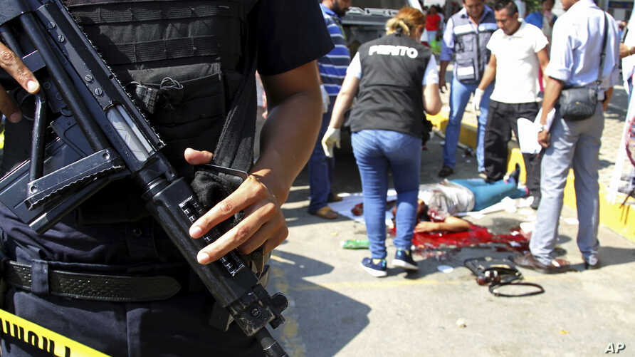 FILE - Police and forensics secure the area where six people were killed, in Acapulco, Mexico, Jan. 4, 2017.