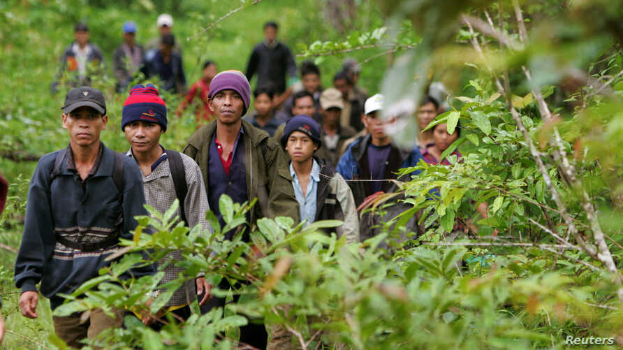Montagnard hill tribesmen walk towards the main road after emerging from dense forest 70 km (43 miles) northeast of Ban Lung, located in Cambodia's northeastern province of Ratanakiri July 22, 2004.