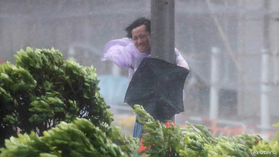 A man holds onto a lamp post against strong winds as Typhoon Hato hits Hong Kong, China, Aug. 23, 2017.