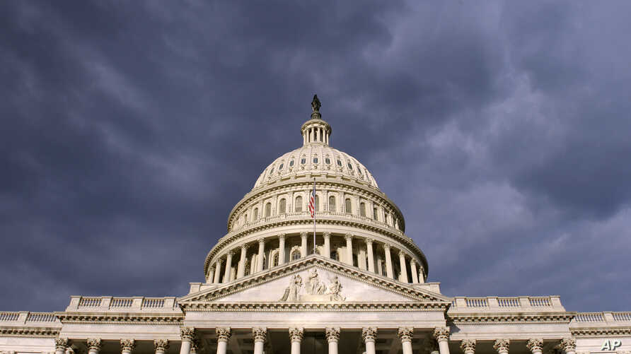 FILE - Dark clouds pass over the Capitol in Washington.