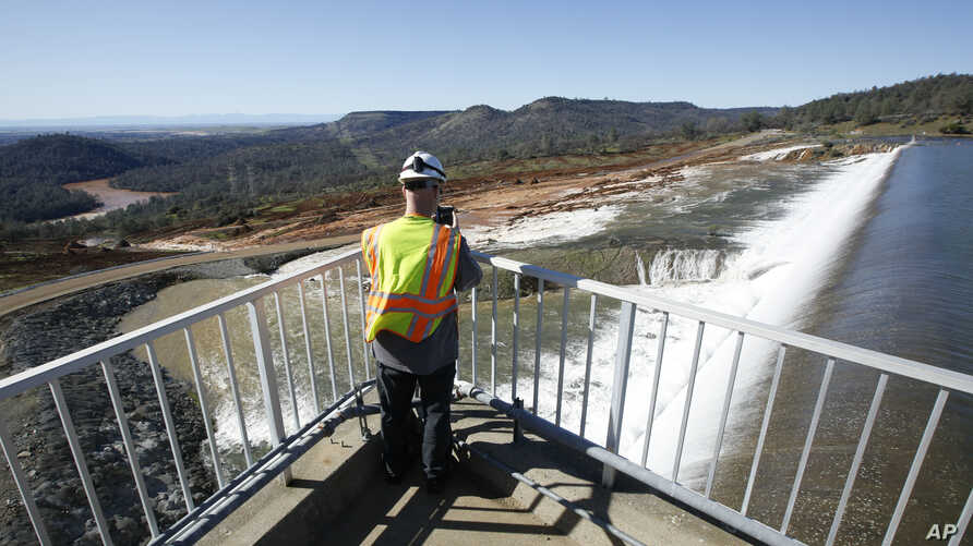 Jason Newton, of the Department of Water Resources, takes a picture of water going over the emergency spillway at Oroville Dam Saturday, Feb. 11, 2017, in Oroville, Calif.