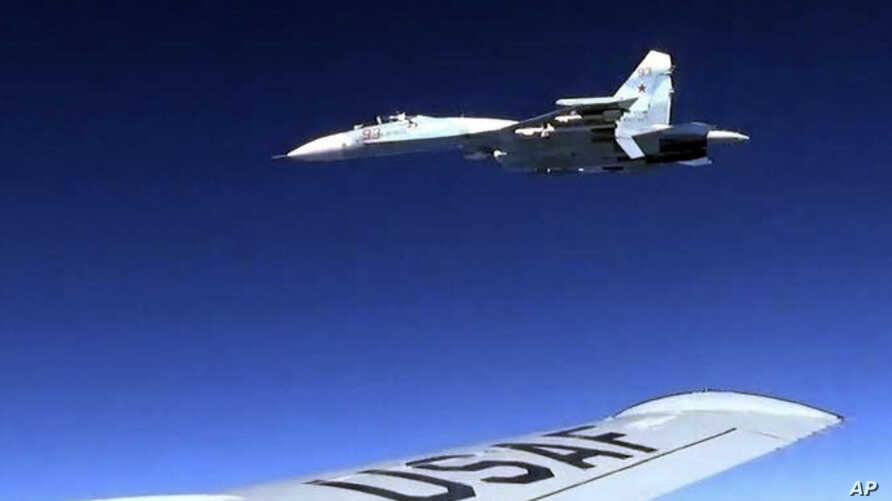 In this image released by the U.S. Air Force, a U.S. RC-135U flying in international airspace over the Baltic Sea, is intercepted by a Russian SU-27 Flanker on June 19, 2017.