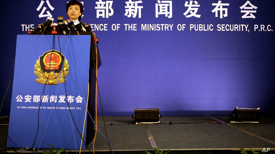 FILE - A spokeswoman for the ministry of public security speaks to the media in Beijing.