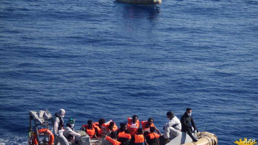 This handout picture released by the Italian Navy on June 6, 2014 shows migrants on boats being arrested and rescued by the Italian army off the coast of Sicily. The Italian navy on June 6 said it had rescued around 2,500 asylum-seekers from 17 boats