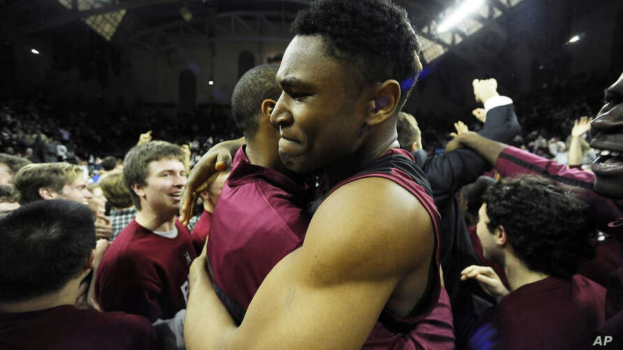 FILE - Harvard's Zena Edosomwan, right, celebrates with a teammate at the end of an NCAA college basketball game in the Ivy League championship playoff against Yale, March 14, 2015.