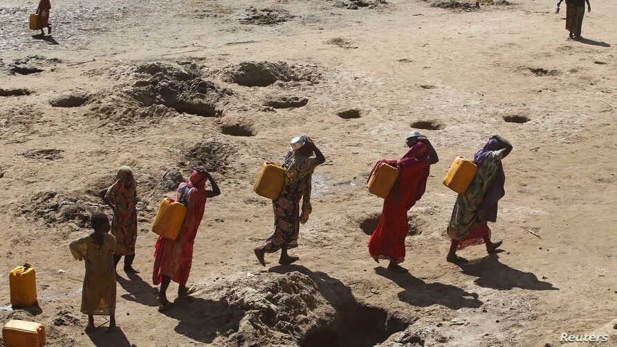 FILE - Women carry jerry cans of water from shallow wells dug from the sand along the Shabelle River bed, which is dry because of drought in Somalia's Shabelle region, March 19, 2016.