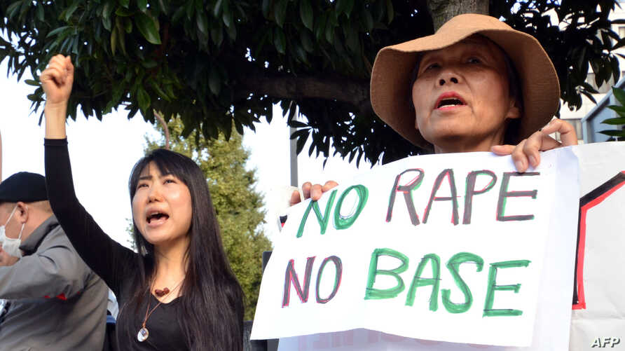 Civic group members shout slogans and hold placards as they attend a protest over the alleged rape of a local woman by two US servicemen in Okinawa, in front of the prime minister's official residence in Tokyo, Oct. 20, 2012.