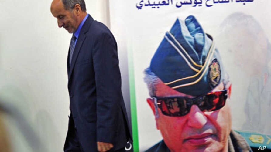 Mustafa Abdel Jalil, chairman of the Libyan National Transitional Council walks in front of a poster of slain Libyan rebels military commander General Abdel Fattah Younes after speaking at a news conference in Benghazi, Libya, August 9, 2011
