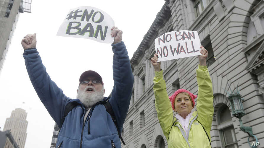 David Pearce, left, and his daughter Crissy Pearce hold signs outside of the 9th U.S. Circuit Court of Appeals in San Francisco, Feb. 7, 2017.