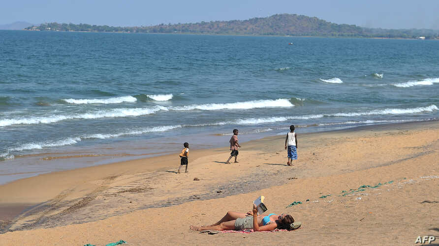 A woman reads a book as young boys pass by on the Saga beach, at Lake Malawi,July 17, 2011.