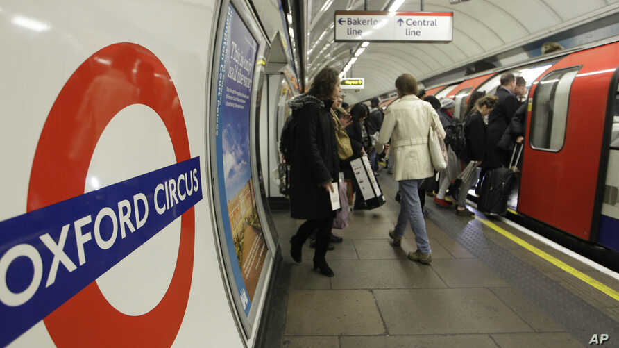 People board an underground 'Tube'  train at Oxford Circus underground station in London.