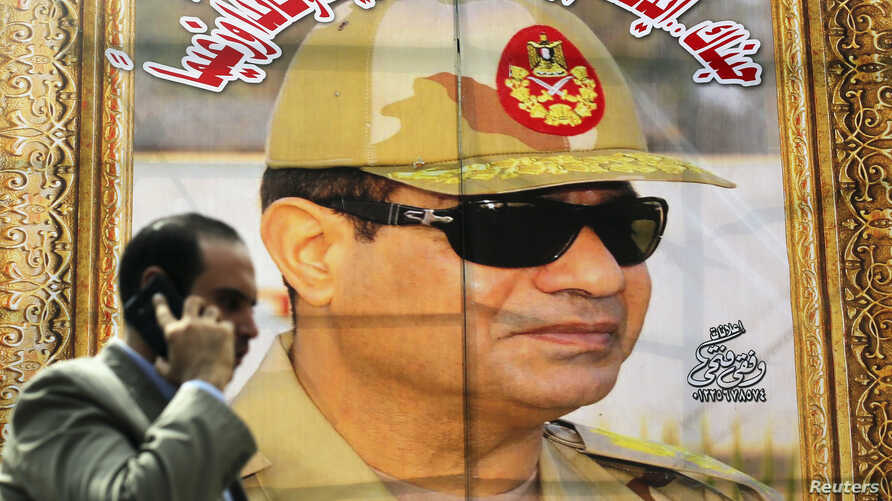 FILE - A man talks on his mobile phone as he walks past a banner of Egypt's president, Abdel-Fattah el-Sissi, at the time still the country's army chief, in downtown Cairo, March 13, 2014.