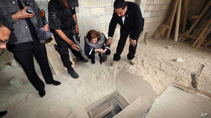 "In this photo provided by Mexico's attorney general, authorities inspect the exit of the tunnel they claim was used by drug lord Joaquin ""El Chapo"" Guzman to break out of the Altiplano maximum security prison in Almoloya, west of Mexico City, July 12..."