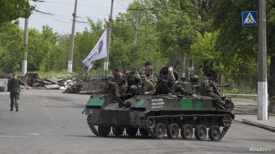 Pro-Russian armed men ride on top of an armoured personnel carrier near the town of Slaviansk, eastern Ukraine, May 5, 2014. Pro-Russian separatists ambushed Ukrainian forces on Monday, triggering heavy fighting on the outskirts of the rebel strongho...