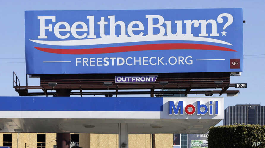 "FILE - This April 1, 2016 file photos shows a billboard above a gas station that reads ""Feel The Burn,"" a play on then-presidential candidate Bernie Sanders' campaign slogan, ""Feel The Bern."" It's actually promoting testing for sexually transmitted d"