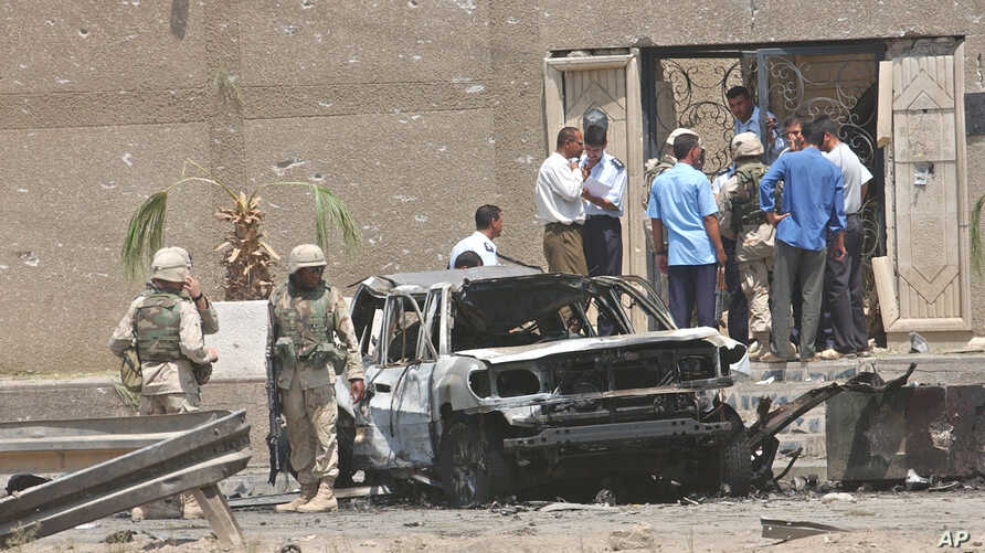 FILE - U.S. troops inspect a destroyed vehicle at the main gate of the Jordanian Embassy after a bomb attack, Aug. 7, 2003, in Baghdad, Iraq.